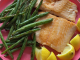 This is an image of salmon with green beans and lemons.